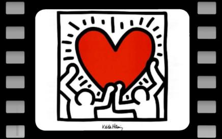 2 personnages portant soulevant un grand coeur rouge